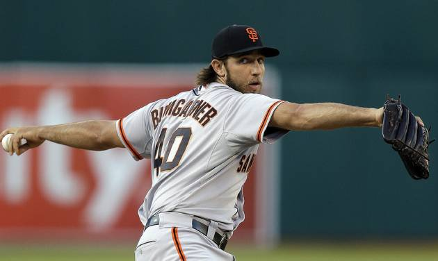 San Francisco Giants' Madison Bumgarner works against the Oakland Athletics in the first inning of a baseball game Tuesday, July 8, 2014, in Oakland, Calif. (AP Photo/Ben Margot)