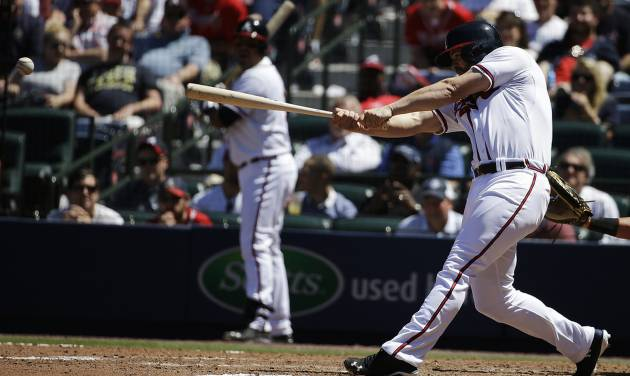 Atlanta Braves' Evan Gattis doubles to score teammates Ramiro Pena and Dan Uggla in the eighth inning of a baseball game against the Miami Marlins, Wednesday, April 23, 2014, in Atlanta. The Braves won 3-1. (AP Photo/David Goldman)