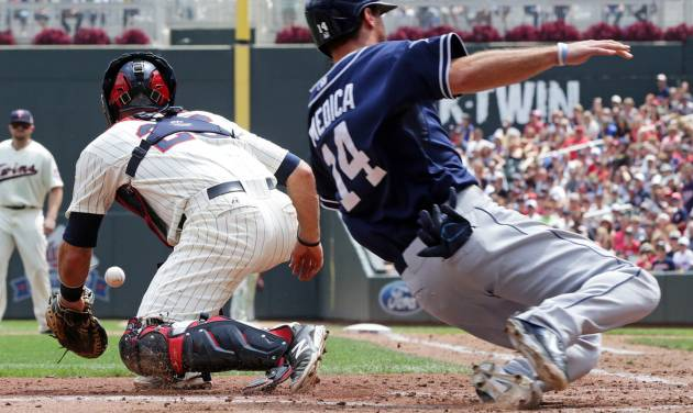 Minnesota Twins catcher Eric Fryer, left, waits for the throw as San Diego Padres' Tommy Medica scores on a double by Jedd Gyorko off Minnesota Twins pitcher Kevin Correia in the fourth inning of a baseball game, Wednesday, Aug. 6, 2014, in Minneapolis. (AP Photo/Jim Mone)