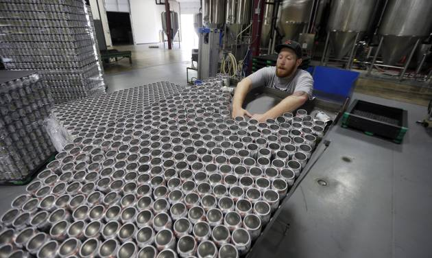 FILE - In this June 3, 2013 file photo, a worker loads empty cans onto the assembly line the Sly Fox Brewing Company in Pottstown, Pa. The Commerce Department reports, on Thursday, July 10, 2014, how much U.S. wholesale businesses adjusted stockpiles in May in response to their sales. (AP Photo/Matt Rourke, File)