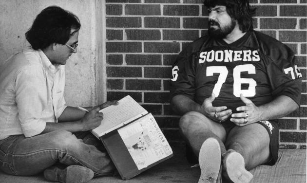 """OU football player Steve """"Dr. Death"""" Williams takes it easy in the shade while being interviewed by Rex Holt of the Stillwater News-Press Sept. 1, 1982. Staff photo by Jim Beckel, The Oklahoman"""