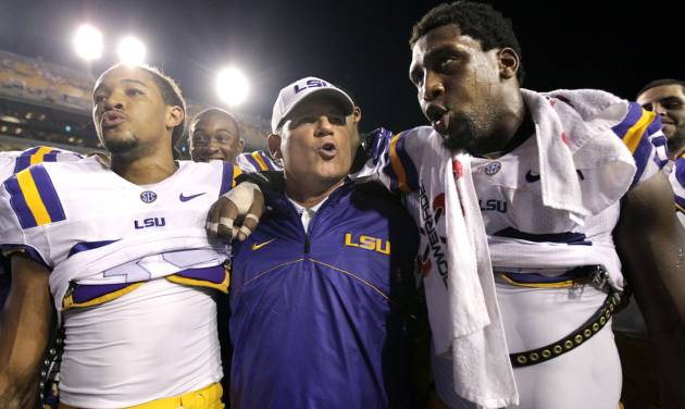 In this Sept. 8, 2012 photo, LSU defensive end Sam Montgomery, right, sings the LSU Alma Mater with head coach Les Miles and cornerback Jalen Collins, left, after their NCAA college football game against Washington in Baton Rouge, La. (AP Photo/Gerald Herbert)