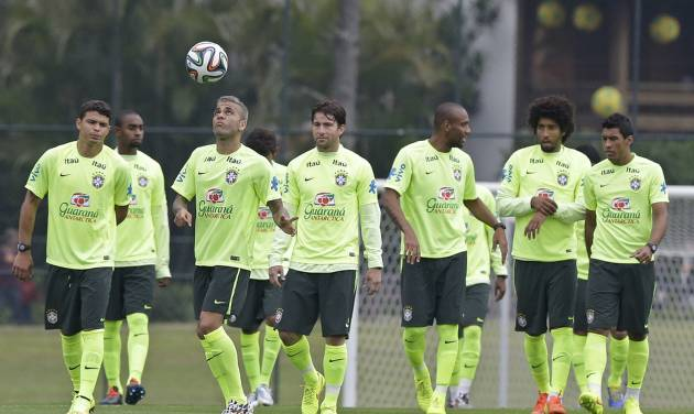Brazil's Dani Alves, third from left, plays with the ball as he practices with teammates during a training session of the Brazilian national soccer team at the Granja Comary training center in Teresopolis, Brazil, Saturday, June 21, 2014. Brazil plays in group A of the 2014 soccer World Cup. (AP Photo/Andre Penner)