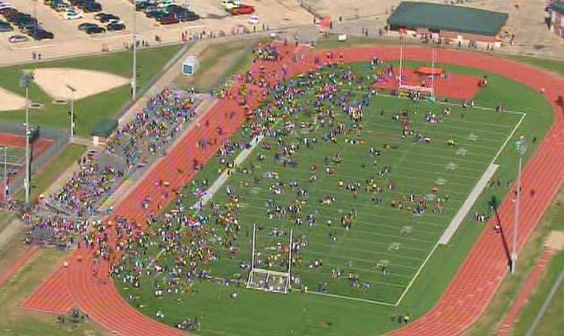 """In this image from video provided by KHOU, students evacuated from Seven Lakes High School in Katy, Texas, mingle on the football field on Monday Jan. 13, 2014 after officials say a """"potential explosive device"""" was identified in the building. After a bomb squad was dispatched, a student is in custody. (AP Photo/KHOU)"""