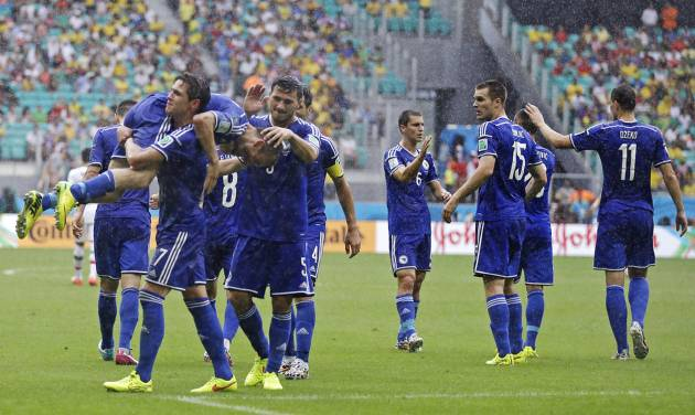 Bosnia's Avdija Vrsajevic is carried by a teammate as he celebrates after scoring his team's third goal during the group F World Cup soccer match between Bosnia and Iran at the Arena Fonte Nova in Salvador, Brazil, Wednesday, June 25, 2014. (AP Photo/Martin Mejia)