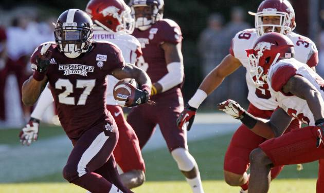 Mississippi State running back LaDarius Perkins (27) runs past Arkansas safety Rohan Gaines (26) and linebacker Jarrett Lake (39) during the fourth quarter of an NCAA college football game in Starkville, Miss., Saturday, Nov. 17, 2012. Mississippi State won 45-14. (AP Photo/Rogelio V. Solis)