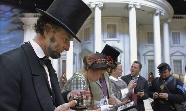 "FILE - In this July 10, 2012 file photo, Abraham Lincoln presenter Fritz Klein joins others in period attire as they learn how to use this ""new-fangled"" mobile ways to access the events and schedules for History Comes Alive at the Abraham Lincoln Presidential Museum in Springfield, Ill. Illinois wants to attract more international tourists and is harnessing the recent popularity of Abraham Lincoln and social media tools as the state looks to market itself overseas with help from a federally funded travel promotional group.   (AP Photo/Seth Perlman, File)"