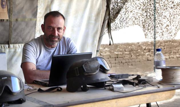 """In this photo released by Spanish newspaper El Periodico de Catalunya on Sunday March 2, 2014, journalist Marc Marginedas who works for the newspaper, sits by his laptop at the Canadian base in Nakhonay, Afganistan in this photo taken on Oct. 10, 2010. Marginedas, who was kidnapped by al-Qaida-linked militants in Syria crossed the border into Turkey on Sunday March 2, 2014  his newspaper reported, as activists said government airstrikes killed at least 13 people in a northwestern border town. Veteran war correspondent Marc Marginedas was abducted on Sept. 4 near Hama by jihadists belonging to the Islamic State of Iraq and the Levant, a breakaway al-Qaida group. He was """"moved repeatedly"""" while in captivity and was accused of spying for the West before his release, his newspaper El Periodico said. (AP Photo/Agustin Catalan, El Periodico de Catalunya)"""