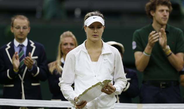 Eugenie Bouchard of Canada holds the runners up trophy after being defeated by Petra Kvitova of Czech Republic in the women's singles final match at the All England Lawn Tennis Championships in Wimbledon, London, Saturday, July 5, 2014. (AP Photo/Sang Tan)