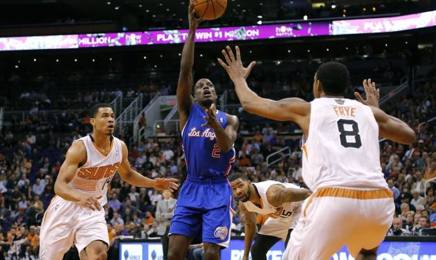Los Angeles Clippers guard Darren Collison (2) passes over Phoenix Suns forward Channing Frye (8) as Suns guard Gerald Green (14) defends during the first half of an NBA basketball game, Wednesday, April 2, 2014,in Phoenix. (AP Photo/Matt York)