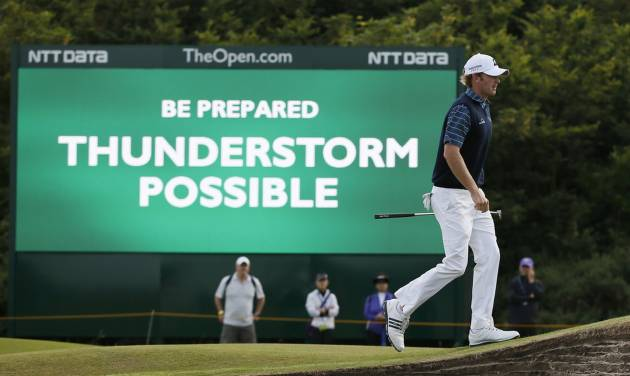 Brandt Snedeker of the US walks past a digital sign showing a weather warning on the second day of the British Open Golf championship at the Royal Liverpool golf club, Hoylake, England, Friday July 18, 2014. (AP Photo/Alastair Grant)