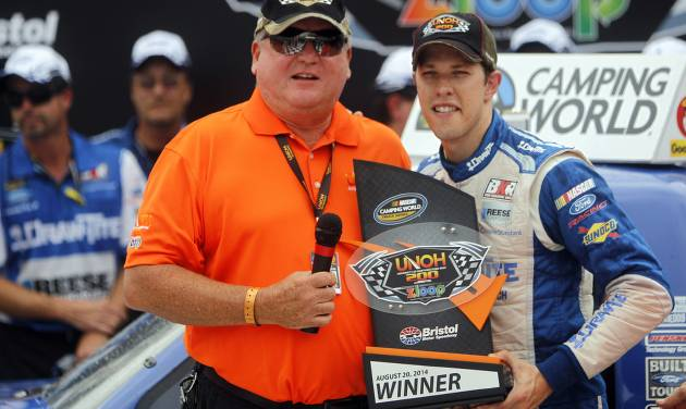 Driver Brad Keselowski, right, accepts the trophy from Dr. Jeff Jarvis after winning the NASCAR UNOH 200 Truck Series auto race on Thursday, Aug. 21, 2014, in Bristol, Tenn. (AP Photo/Wade Payne)