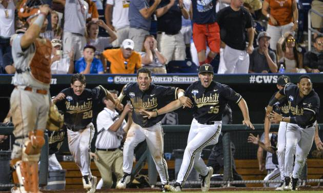 Vanderbilt players dash from the dugout as a single by Tyler Campbell in the 10th inning scored Rhett Wiseman for a 4-3 win over Texas in an NCAA baseball College World Series game in Omaha, Neb., Saturday, June 21, 2014. Vanderbilt advances to the championship series. (AP Photo/Ted Kirk)