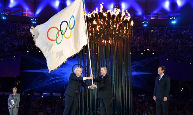 The Olympics flag is handed from London Mayor, Boris Johnson, second from left, to the International Olympic Committee President Jacques Rogge, as the Mayor of Rio de Janeiro, Eduardo Paes, right, watches during the Closing Ceremony of the 2012 Summer Olympic on Sunday, Aug. 12, 2012, in London. (AP Photo/Jeff J Mitchell, Pool)