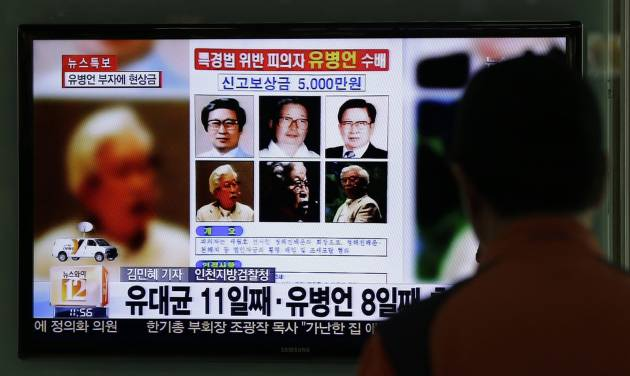 A man watches the TV news program on the reward poster of Yoo Byung-eun at the Seoul Train Station in Seoul, South Korea, Friday, May 23, 2014. South Korea is offering a big bounty to find the mysterious billionaire thought to be the owner a ferry that sank last month, leaving more than 300 people dead or missing. (AP Photo/Lee Jin-man)
