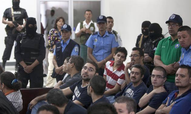 CORRECTS YEAR - Mexican citizens, alleged members of an organized crime group, attend the reading of their sentence at court in Managua, Nicaragua, Friday, Jan. 18, 2013. A Nicaraguan judge has sentenced 18 Mexicans who posed as a television crew to 30 years in prison for drug trafficking and money laundering stemming from $9.2 million found in their news vans. (AP Photo/Mayerling Garcia)
