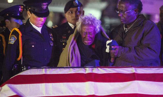 Clara Gantt, the 94-year-old widow of U.S. Army Sgt. Joseph Gantt, weeps in front of her her husband's casket after it was lowered from the plane, Friday, Dec. 20, 2013 in Los Angeles. Sixty-three years after Army Sgt. 1st Class Joseph E. Gantt went missing in action during the Korean War, his remains were returned to his 94-year-old widow in a solemn ceremony at Los Angeles International Airport before dawn Friday.  (AP Photo/Los Angeles Times, Andrew Renneisen, Pool)