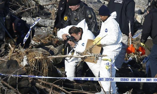 After discovering an arm, torso and legs Thursday, police photograph the scene as they continue the search for human remains along a rocky shoreline in the Queens borough of New York, Friday, Jan. 17, 2014.  New York Police were investigating whether the remains found Thursday could be those of autistic teen Avonte Oquendo, who walked out of his school and vanished more than three months ago, a law enforcement official said Friday. (AP Photo/Jason DeCrow)