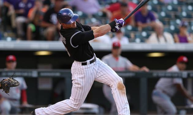 Colorado Rockies' Drew Stubbs follows through with his swing after connecting for a three-run walkoff home run against the Cincinnati Reds in the ninth inning of the Rockies' 10-9 victory in a baseball game in Denver, Sunday, Aug. 17, 2014. (AP Photo/David Zalubowski)