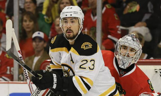Boston Bruins center Chris Kelly (23) looks for a pass as Chicago Blackhawks goalie Corey Crawford (50) looks on in the first period during Game 2 of the NHL hockey Stanley Cup Finals, Saturday, June 15, 2013, in Chicago. (AP Photo/Nam Y. Huh)