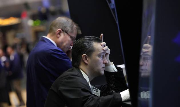 Trader Theodore Nelson, right, is reflected on a panel as he works on the floor of the New York Stock Exchange Monday, June 4, 2012. The Dow Jones industrial average opened at its lowest level since December after a 275-point sell-off on Friday caused by grim economic signals, especially a dismal report on the U.S. labor market. (AP Photo/Richard Drew)