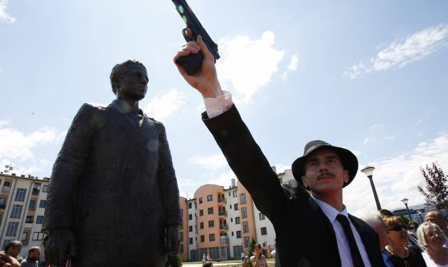 Bosnian actor Jovan Mojsilovic poses with a plastic replica gun  during ceremony of unveiling statue of Gavrilo Princip in Istocno Sarajevo, on Friday, June 27, 2014. Marking the centennial of the beginning of World War I in their own way, Bosnian Serbs have unveiled a monument of Gavrilo Princip in the Eastern part of Sarajevo to the man who ignited the war by assassinating the Austro-Hungarian crown prince on June 28, 1914.(AP Photo/Amel Emric)
