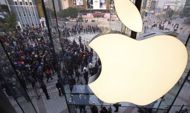 FILE - In this Oct. 20, 2012 photo, people line up to enter a newly-opened Apple Store in Wangfujing shopping district in Beijing. Exxon has once again surpassed Apple as the world's most valuable company after the iPhone and iPad maker saw its stock price falter, according to reports Friday, Jan. 25, 2013. Apple first surpassed Exxon in the summer of 2011. The two companies traded places through that fall, until Apple surpassed Exxon for good in early 2012. (AP Photo/Andy Wong, File)