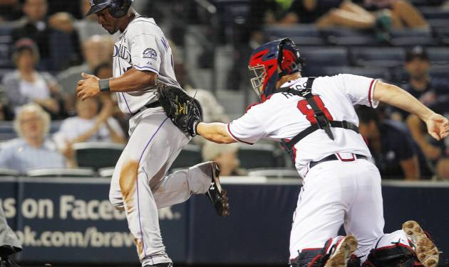 Colorado Rockies' Chris Nelson, left, scores on a hit by DJ LeMahieu as Atlanta Braves catcher David Ross (8) can't hang on to the ball in the eighth inning of a baseball game Tuesday, Sept. 4, 2012, in Atlanta. (AP Photo/John Bazemore)