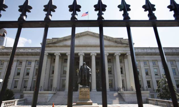 FILE - In this Monday, Aug. 8, 2011, file photo, a statue of former Treasury Secretary Albert Gallatin stands outside the Treasury Building in Washington. The Treasury Department reports on the federal budget picture for April and for the fiscal year thus far on Monday, May 12, 2014. (AP Photo/Jacquelyn Martin, File)