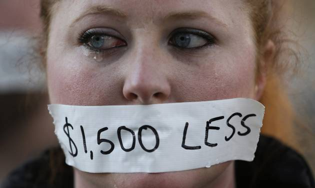 A silent protester cries while wearing a sticker over her mouth signifying the loss in wages from the right-to-work law in Lansing, Mich., Wednesday, Dec. 12, 2012. Michigan became the 24th state with a right-to-work law after Gov. Rick Snyder signed the bill Tuesday. (AP Photo/Paul Sancya)
