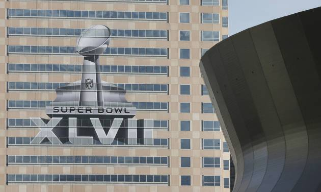 FILE - The NFL Super Bowl XLVII NFL football game logo is seen past the Mercedes-Benz Superdome on the face of an office building as preparations take place in this Sunday, Jan. 27, 2013 file photo taken in New Orleans. New Orleans has celebrated plenty of milestones on its slow road to recovery from Hurricane Katrina, but arguably none is bigger than hosting its first Super Bowl since the 2005 storm left the city in shambles. The Baltimore Ravens and San Francisco 49ers are scheduled to play in Super Bowl XLVII on Sunday, Feb. 3. (AP Photo/Patrick Semansky, File)