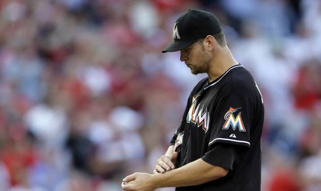 Miami Marlins starting pitcher Josh Johnson, right, walks the mound after giving up a two-run home run to Philadelphia Phillies' Jimmy Rollins, left, in the seventh inning of a baseball game on Wednesday, Sept. 12, 2012, in Philadelphia. Philadelphia won 3-1. (AP Photo/Matt Slocum)
