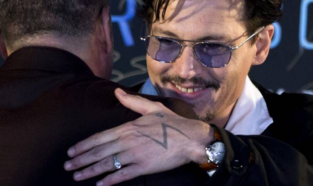 """Actor Johnny Depp, with a diamond ring on his left hand, attends a promotional event for his new movie """"Transcendence"""" in Beijing, China, Monday, March 31, 2014.  Johnny Depp showed off a diamond engagement ring that he called a """"chick's ring"""" on Monday, indirectly confirming rumors of his engagement to actress Amber Heard. (AP Photo/Alexander F. Yuan)"""