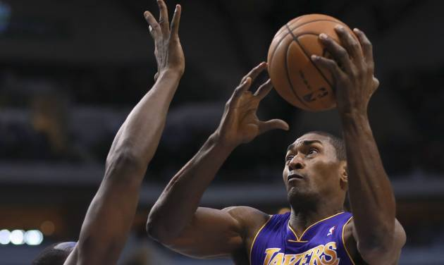 Los Angeles Lakers small forward Metta World Peace (15) drives on Dallas Mavericks' Elton Brand (42) during the first half of an NBA basketball game on Saturday, Nov. 24, 2012, in Dallas. (AP Photo/Michael Mulvey)