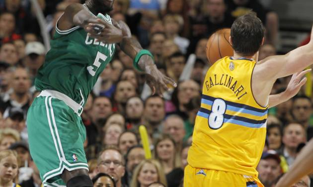 Boston Celtics forward Kevin Garnett, left, throws the ball at Denver Nuggets forward Danilo Gallinari, of Italy, in an efort to keep the ball in play late in the fourth quarter of the Nuggets' 97-90 victory in an NBA basketball game in Denver on Tuesday, Feb. 19, 2013. (AP Photo/David Zalubowski)