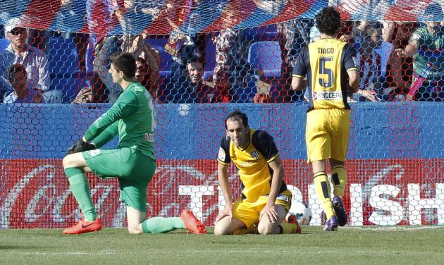 Atletico de Madrid's goalkeeper Thibaut Courtois from Belgium, left, and Diego Godin from Uruguay, center, stay on the ground after Levante scored a second goal during a Spanish La Liga soccer match at the Ciutat de Valencia stadium in Valencia, Spain, on Sunday May 4, 2014. (AP Photo/Alberto Saiz)