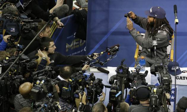 Seattle Seahawks' Richard Sherman takes some pictures during media day for the NFL Super Bowl XLVIII football game Tuesday, Jan. 28, 2014, in Newark, N.J. (AP Photo/Charlie Riedel)