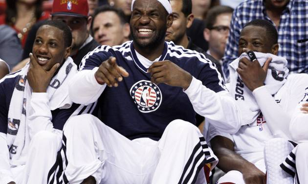 Miami Heat forward LeBron James, center, laughs with guards Mario Chalmers, left, and Dwyane Wade as they sit on the bench during the end of the second half of an NBA basketball game against the Brooklyn Nets, Wednesday, Nov. 7, 2012 in Miami. The Heat defeated the Nets 103-73. (AP Photo/Wilfredo Lee)