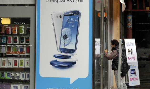 FILE - In this a, Monday, Nov. 5, 2012, file photo, a man windowshop at a mobile phone shop near advertisement of Samsung's Galaxy S III smartphone in Seoul, South Korea. Samsung Electronics Co. said Monday, Jan. 14, 2013, it has sold more than 100 million Galaxy S smartphones since the first model in the series was released nearly three years ago. (AP Photo/Lee Jin-man, Photo)