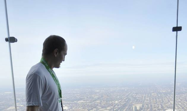 """Zac Vawter stands on """"The Ledge"""" of the Willis Tower in Chicago after walking up the stairs of the building Sunday, Nov. 4, 2012, to become the first person to climb the 103 floors of one of the world's tallest skyscrapers with a bionic leg. Vawter was wearing a prosthetic leg controlled by his mind while participating in """"SkyRise Chicago."""" (AP Photo/Chicago Sun-Times, Brian Jackson) CHICAGO LOCALS OUT, MAGS OUT"""