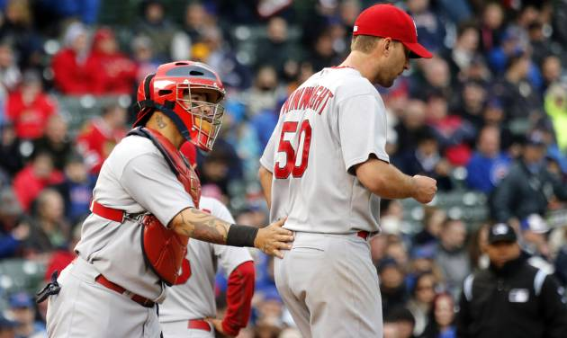 St. Louis Cardinals catcher Yadier Molina, left, pats starting pitcher Adam Wainwright during the fifth inning of a baseball game against the Chicago Cubs, Friday, May 2, 2014, in Chicago. (AP Photo/Charles Rex Arbogast)