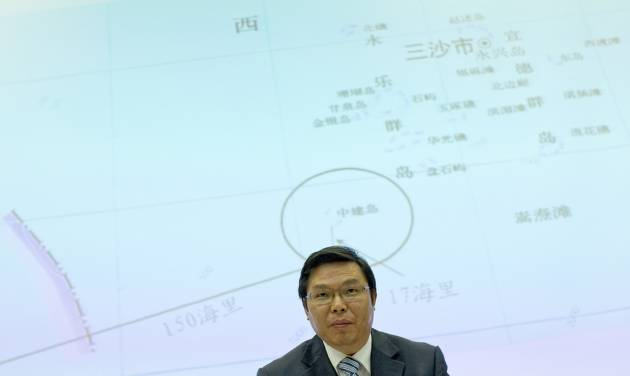 Yi Xianliang, deputy director-general of Chinese Ministry of Foreign Affairs' Department of Boundary and Ocean Affairs, stands up, in front of a map showing a disputed zone in South China Sea, to leave a press conference in Beijing, China, Thursday, May 8, 2014. Chinese and Vietnamese ships were locked in a tense standoff Thursday in disputed waters where Beijing is trying to set up an oil rig, a Vietnamese commander said, as the United States urged both sides to de-escalate tensions in the most serious incident in the South China Sea in years. (AP Photo/Alexander F. Yuan)