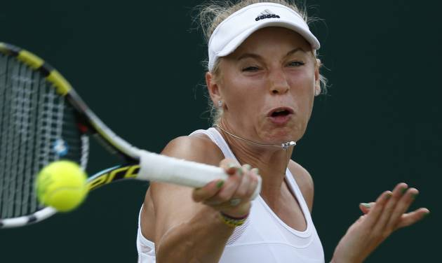 Caroline Wozniacki of Denmark plays a return to Barbora Zahlavova Strycova of the Czech Republic  during their women's singles  match at the All England Lawn Tennis Championships in Wimbledon, London, Monday, June 30, 2014. (AP Photo/Sang Tan)