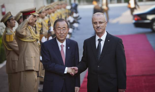 United Nations Secretary-General Ban Ki-moon, left, shakes hands with Palestinian Prime Minister Rami Hamdallah upon his arrival in the West Bank city of Ramallah, Tuesday, July 22, 2014. The two men were set to hold a joint news conference regarding the Israel-Hamas conflict. (AP Photo/Majdi Mohammed)