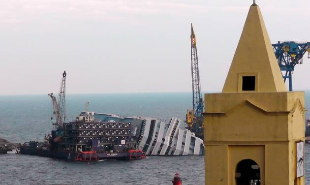 "FILE - This Jan. 11, 2013 file photo shows the cruise ship Costa Concordia leaning on its side, near the shore of the Tuscan island of Giglio, Italy.  Thirty-two people died when the ship ran aground on Jan. 13, 2012. Cruise watchers looking back at the industry's past year say the Concordia disaster affected everything from prices to safety drills to first-time cruisers, but bookings appear to be picking up as the 2013 cruise booking season gets under way. The first three months of each year are known as ""wave season,""a period when many cruisers book trips as they plan ahead for summer vacations.  (AP Photo/Paolo Santalucia, file)"