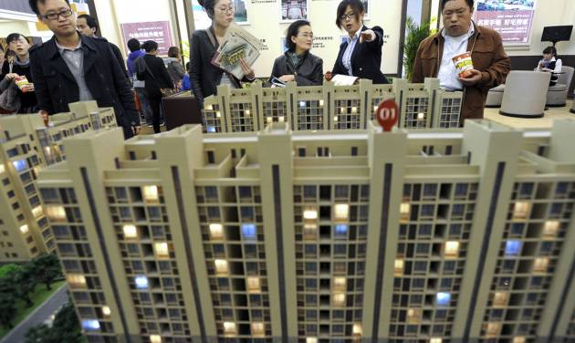 In this April 21, 2012 photo, people check a scale model of a housing project at a real estate fair in Nanjing, in eastern China's Jiangsu province. State media reported Sunday, July 8, 2012, that China's top economic official has ordered local officials to enforce rules aimed at cooling a surge in housing prices. (AP Photo) CHINA OUT