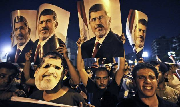 In this Wednesday, July 10, 2013 photo, supporters of ousted Egypt's President Mohammed Morsi, hold posters of him as they protest during the Islamic month of Ramadan, in Nasr City, Cairo, Egypt. As the sun set on the first day of the Islamic holy month of Ramadan, families across Cairo gathered for the fast-breaking iftar meal in a country that in the last two weeks has seen protests by millions, a coup against an elected president and the deaths of dozens of people in clashes with the military. Ramadan is traditionally a time of personal reflection and feeling a sense of brotherhood with fellow Muslims, but in the aftermath of the military overthrow of President Mohammed Morsi, the divisions among Egyptians extend even down to this traditional meal. (AP Photo/Hussein Malla)