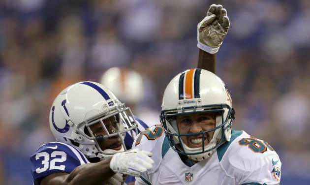 FILE - In this Nov. 4, 2012 file photo,Miami Dolphins wide receiver Brian Hartline, right, tries to break the tackle of Indianapolis Colts cornerback Cassius Vaughn during the first half of an NFL football game in Indianapolis. The veteran receiver agreed to a five-year deal for nearly $31 million to remain with the Miami Dolphins, his agent said Friday, March 8, 2013.  (AP Photo/Darron Cummings, File)