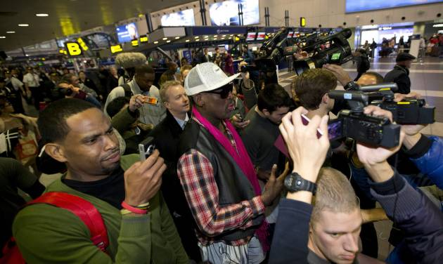 Former NBA basketball player Dennis Rodman, center, is surrounded by media as he arrives at the departure hall of Beijing International Capital Airport in Beijing Monday, Jan. 6, 2014. Rodman says he's going forward with an exhibition game including former NBA players in North Korea because he wants to connect with its people and let others know the sheltered communist country isn't so bad. (AP Photo/Andy Wong)