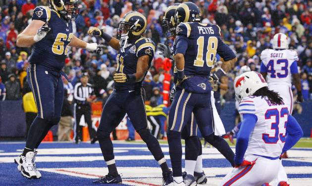 St. Louis Rams wide receiver Brandon Gibson (11) celebrates with teammates including guard Harvey Dahl (62) and wide receiver Austin Pettis (18) after catching a touchdown pass from quarterback Sam Bradford, not pictured, as Buffalo Bills cornerback Ron Brooks (33) reacts during the second half of an NFL football game, Sunday, Dec. 9, 2012, in Orchard Park, N.Y. The Rams won 15-12. (AP Photo/Bill Wippert)